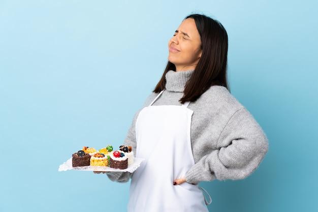Cukiernik z wielkim tortem na niebieskiej ścianie cierpiący na bóle kręgosłupa