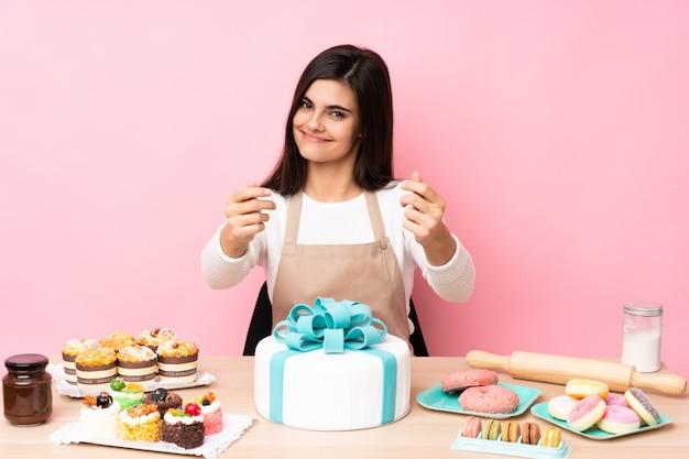 Cukiernik z wielkim tortem w stole nad różową ścianą robi pieniądze gestem