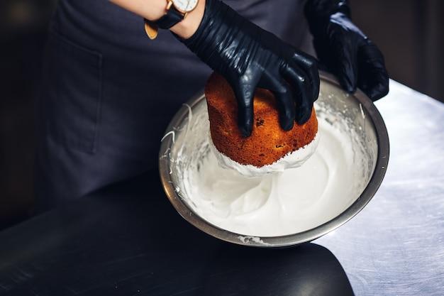 Cukiernik zanurza wierzch ciasta wielkanocnego w kremie proteinowym.