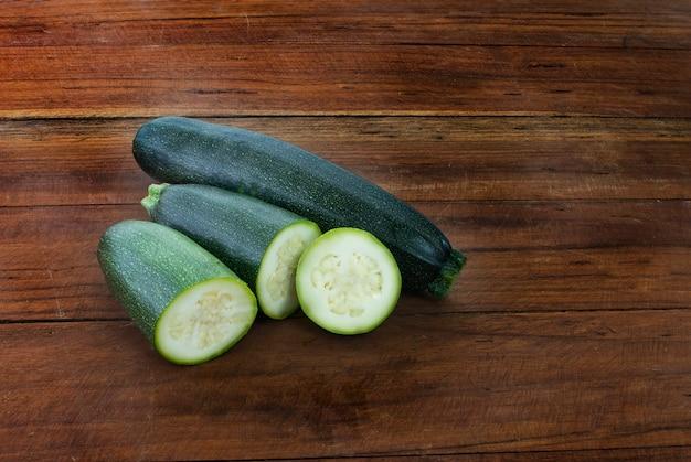 Cukinia świeży zielony bio na drewnianym stole. organiczne warzywa sezonowe.
