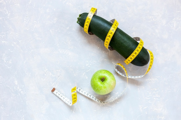 Cukinia, zielone jabłko i centymetr. świeże owoce i warzywa