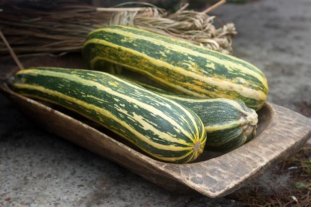 Cukinie lub cukinia i pakiet słomy w drewnianej rynnie na targach rolnych.