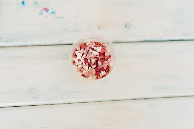 Cukrowe serca leżą na drewnianym.