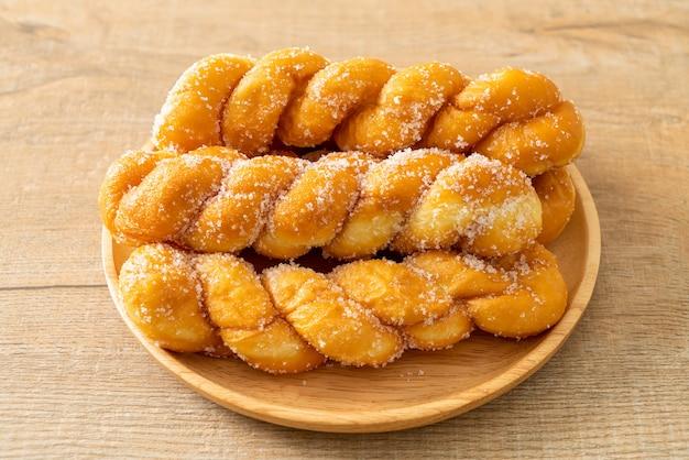 Cukrowy pączek w kształcie spirali na drewnianym talerzu