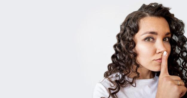 Culry kobieta robi znak ciszy z miejsca na kopię