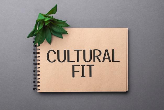 Cultural fit tekst na notatniku w kolorze rzemieślniczym i zielona roślina na ciemnym tle