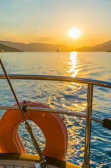 Cumowanie jest ustalane na szynach podczas ruchu jachtu. czarnogóra, morze adriatyckie, zachód słońca.