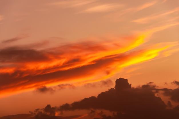 Cumulonimbus pomarańczowy i żółty w ukośnej formacji oświetlony światłem zachodu słońca