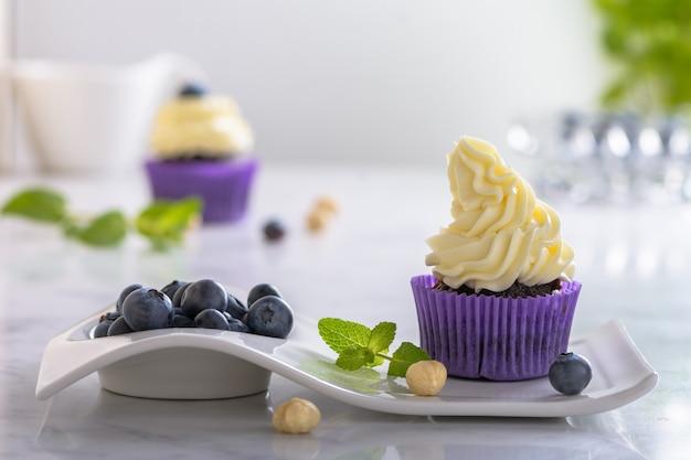 Cupcake na białym talerzu z jagodami i orzechami laskowymi w fioletowym opakowaniu na marmurowym blacie.