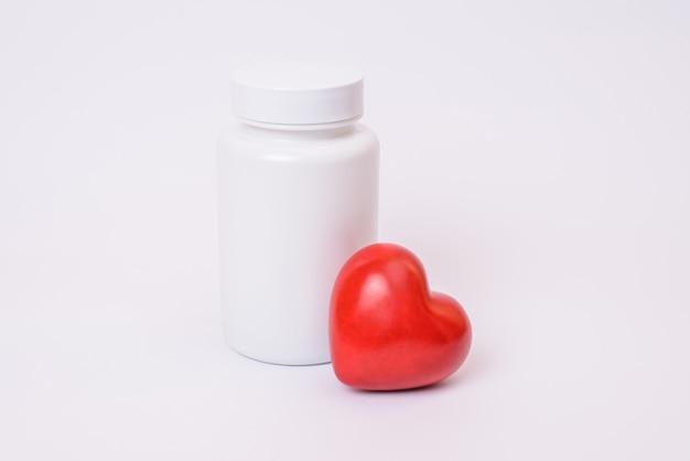 Cure fiolka wzór szablonu lekarstwo copyspace copyspace koncepcji klinicznej. zbliżenie na zdjęcie dużego białego bez miejsca na etykietę na tekst z małym czerwonym błyszczącym sercem na białym tle
