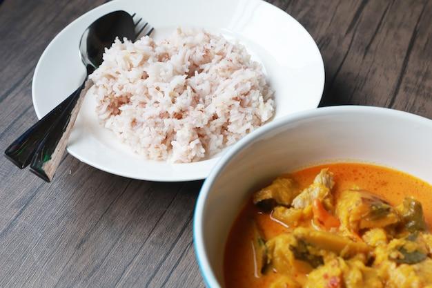 Curry bania w białym pucharze i ryż na drewnianym stole