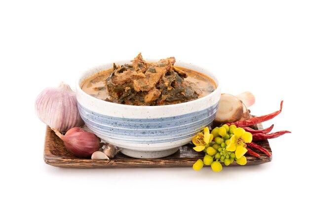 Curry cassia z grillowaną wieprzowiną i składnikami na białym tle.