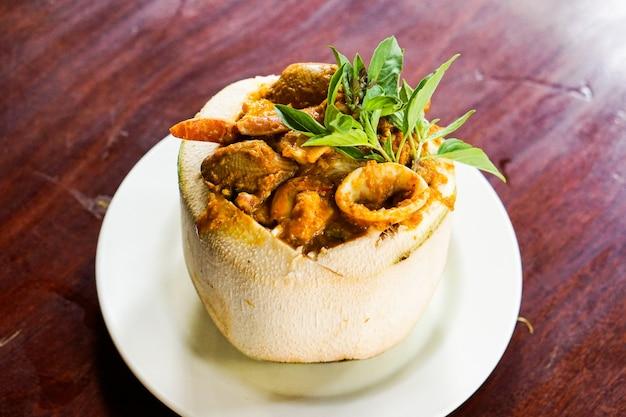 Curry lejący się owoce morza w kokosowej filiżance na czerwonym stołowym tle