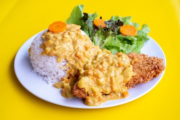 Curry smażył ciasto naleśnikowe z ryżem na talerzu nad żółtym tłem. widok z góry, leżał płasko.