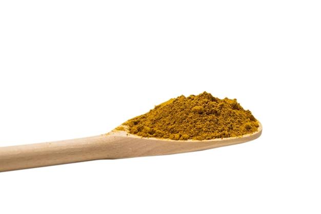 Curry w drewnianą łyżką na białym tle