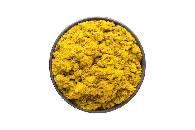 Curry w proszku w glinianej misce na białym tle