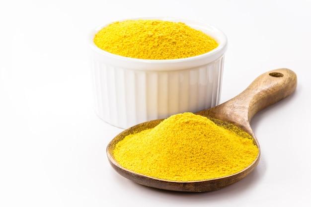Curry w proszku z łyżką i miską na na białym tle