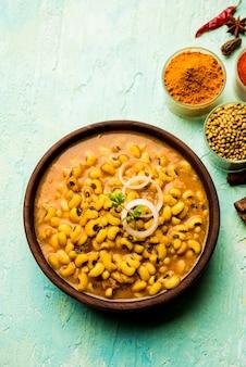 Curry z fasolą black eyed kidney podawane w misce z naanem i ryżem