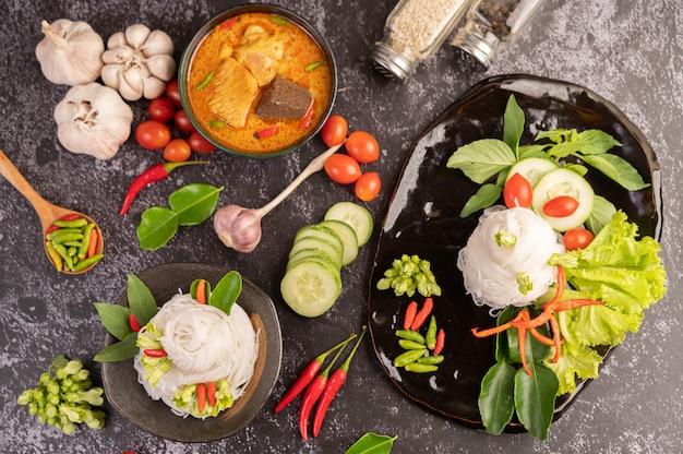 Curry z kurczaka w czarnej filiżance z makaronem ryżowym.