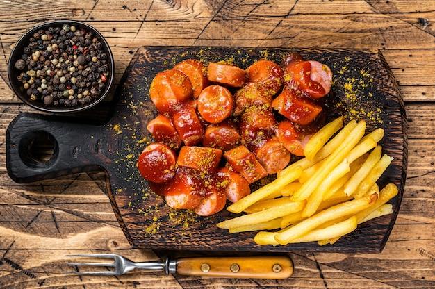 Currywurst sausages street food serwował frytki na drewnianej desce. drewniane tła. widok z góry.