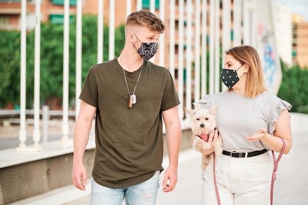 Curvy kobieta i przystojny mężczyzna jest ubranym twarzy maskę bierze spacer z ich psem - coronavirus pojęcie