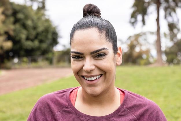 Curvy kobieta uśmiechając się na zewnątrz w parku miejskim - skupić się na twarzy