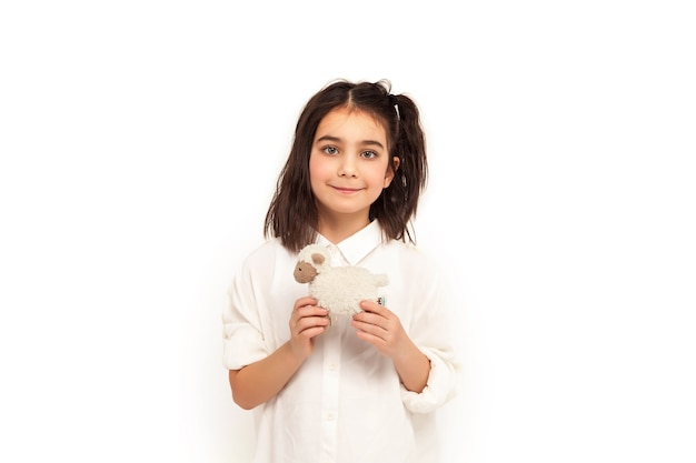Cute 6-7 letnia dziewczyna w domowej koszuli z zabawką na na białym tle patrzy na aparat. zabawa koncepcyjna i rekreacja dla dzieci. małe dziecko w ubraniu pozuje i pokazuje emocje. skopiuj miejsce