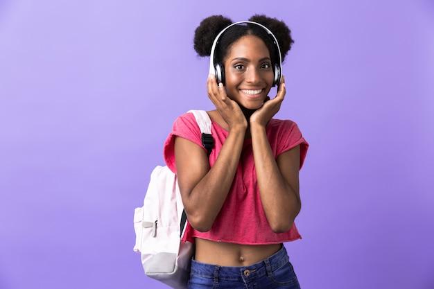Cute african american kobieta noszenie plecaka i białych słuchawek, na białym tle