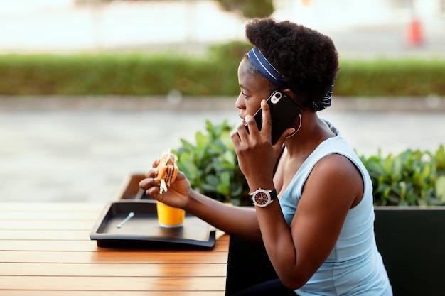 Cute african kobieta obiad na świeżym powietrzu w kawiarni miejskiej. dziewczyna rozmawia przez telefon podczas lunchu.