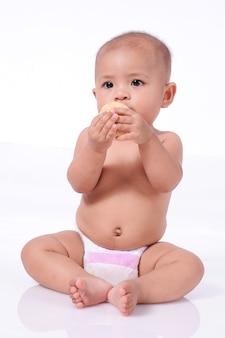 Cute asian baby girl noszenie pieluchy gospodarstwa herbatniki