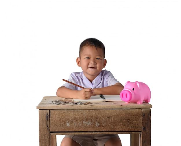 Cute asian country boy zanotuj wpływy z dochodów i monety z piggy bank na białym tle