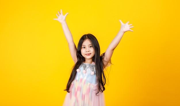 Cute asian dziewczyna z długimi włosami i ładną sukienką dla dzieci wziąć na białym tle piękny portret na żółtym tle.