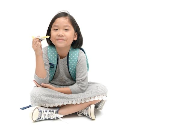 Cute asian girl student z plecakiem siedzieć i trzymając samolot zabawka samodzielnie na białym tle, educ