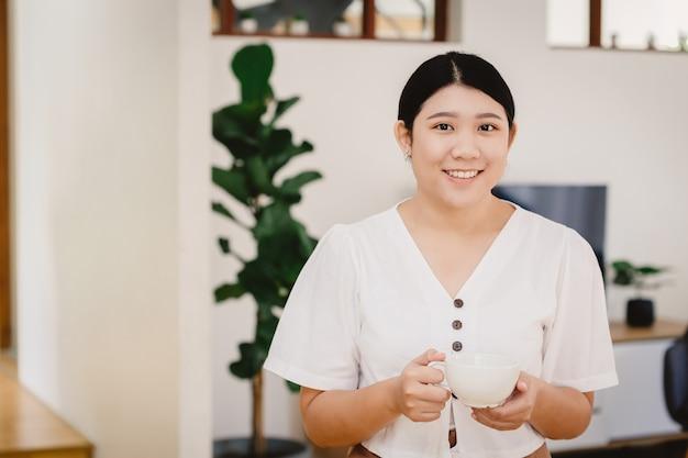 Cute asian girl teen uchwyt kubek kubek i uśmiech do diety picia herbaty ziołowej lub zdrowego napoju w domu.