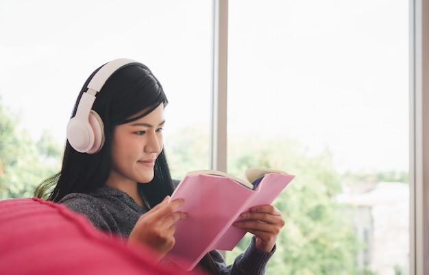 Cute asian kobieta siedzi na kanapie rano i czyta książkę