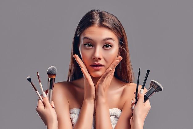 Cute atrakcyjna dziewczyna z pędzle do makijażu na białym tle na szarym tle. salon kosmetyczny, makijaż.