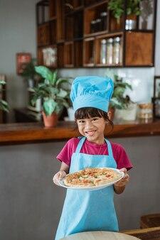 Cute azjatyckich dziewczynka trzyma talerz z pyszną pizzą