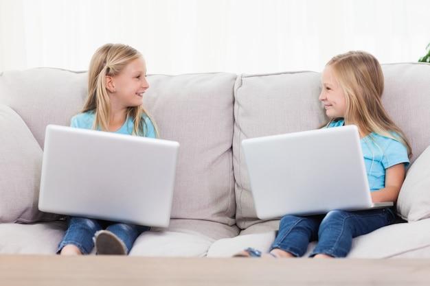 Cute bliźnięta za pomocą laptopy siedzi na kanapie