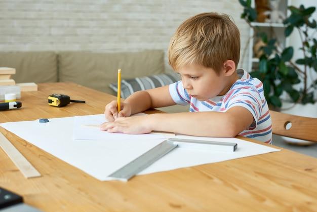 Cute boy rysowanie planów pracy