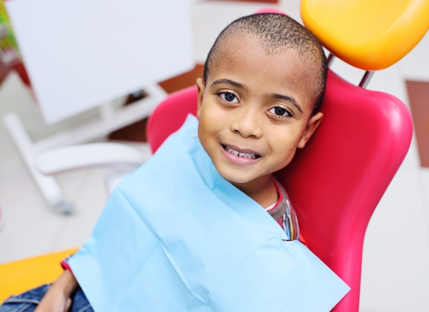 Cute czarny chłopczyk african american uśmiechnięty siedzi na fotelu dentystycznym