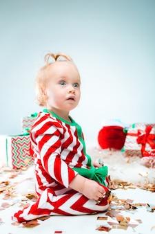 Cute dziewczynka 1 rok w pobliżu santa hat pozowanie na boże narodzenie
