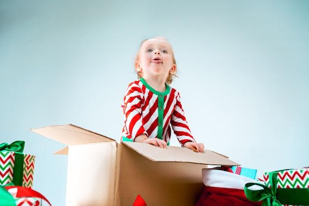 Cute dziewczynka 1 rok życia siedzi w pudełku na boże narodzenie