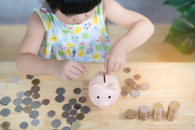 Cute dziewczynka azji upuść monety w skarbonce, koncepcja oszczędności.