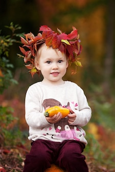 Cute dziewczynka bawi się szpiku warzyw w parku jesień. jesienne zajęcia dla dzieci. halloween i święto dziękczynienia zabawa dla rodziny.