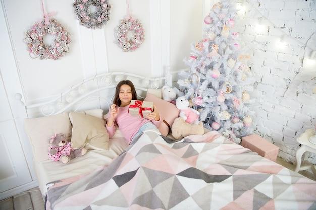 Cute dziewczynka dziecko z prezentem xmas. szczęśliwa dziewczynka świętować ferie zimowe. czas świąt. rano przed bożym narodzeniem. szczęśliwego nowego roku. dostawa prezentów świątecznych. wakacje w domu. dekoracje.