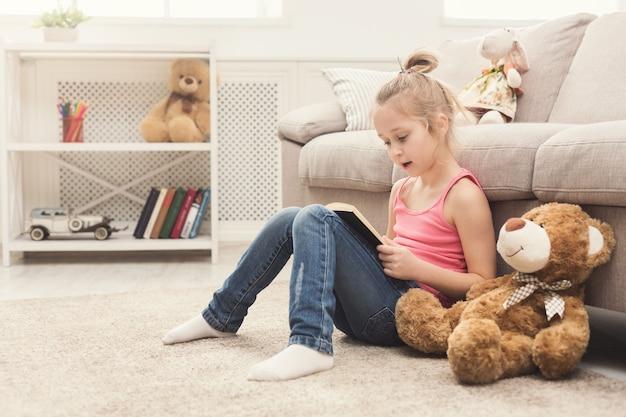 Cute dziewczynka i jej czytanie książki misia. ładne dziecko w domu, siedząc na podłodze obok sofy ze swoją ulubioną zabawką, koncepcją edukacji i wczesnego rozwoju, kopia przestrzeń