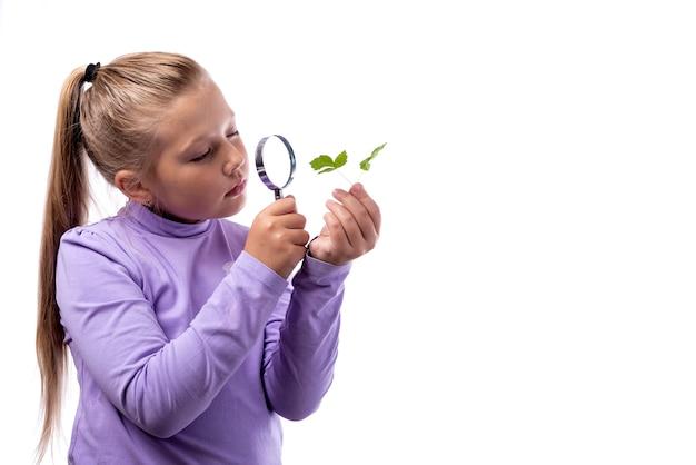Cute dziewczynka kaukaski patrząc na roślinę przez lupę na białym tle.