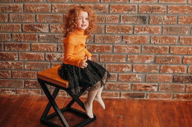 Cute dziewczynka siedzi na krześle w nowym salonie. zdjęcie z miejscem na kopię