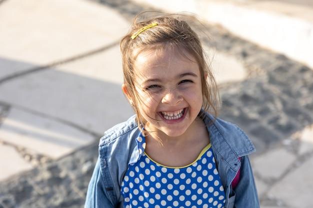 Cute dziewczynka uśmiecha się i patrzy w kamerę.