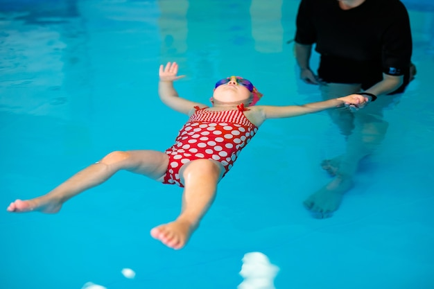 Cute dziewczynka w czerwonym stroju kąpielowym i specjalne okulary, grając w basenie.